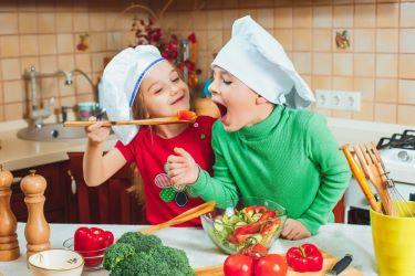 glueckliche-familie-lustige-kinder-bereiten-den-frischen-gemuesesalat-in-der-kueche-vor_155003-2571